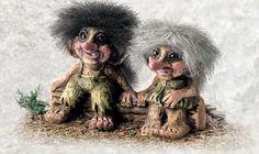two cute trolls sitting on a stump.