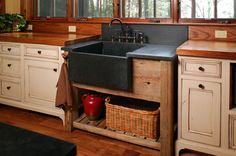 This rustic kitchen has a stand-alone farmhouse apron sink in black stone sitting on a wooden base cabinet with an open shelf. Here, a honed absolute black granite sink, counter and backsplash sit on a wooden base that looks like a vanity, with an open shelf on the bottom. A bridge-style faucet in an oil-rubbed bronze finish completes the look. Paul Bradham