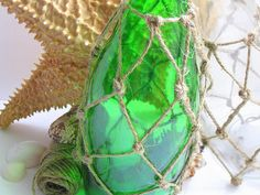 How to make a knotted jute fish net for a bottle!  So cute...add a little sand and some small shells.  Love this!