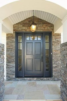 Traditional Front Door with Stacked stone wall, Transom window, exterior stone floors