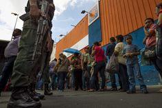 La gente se coloca en la cola fuera de un supermercado en Venezuela.