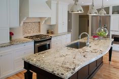 THE GRANITE!! Kitchen. white wooden kitchen cabinet and white granite countertop with silver sink of brown wooden kitchen island on laminate flooring also silver pendant lamp on ceiling. Minimalist Off White Kitchen Cabinets Perfecting Your Kitchen Decoration