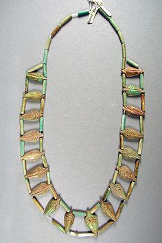 Almost time for autumn! Collected during an excavation of the Ancient Egyptian city of Tebtunis in 1900, this necklace dates to the Late Middle Kingdom about 4,000 years ago. The leaf-shaped and tubular beads are possibly Egyptian faience, a non-clay-based ceramic made of crushed quartz or sand that is often colored turquoise or blue when fired due to the presence of metal oxides. PAHMA 6-20902. #hearstmuseum #egypt #necklace #faience #leaves