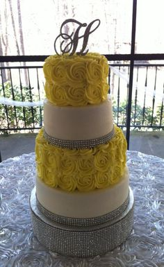 Beautiful 4 tier wedding cake with yellow swirl roses and bling ribbon. Delivered to Castle McCulloch in Jamestown, NC.
