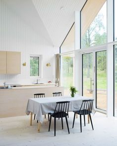 This house features an open-plan living, kitchen and dining area, and features a facade that is entirely glazed.