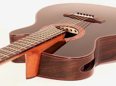 Ergo Guitars - wedge-shaped body, elevated finger board and patented ultra-low-mass sound board - To compensate for the soundboard's inward tilt, the ergo fingerboard rotates outward away from the player, maximizing left hand playing comfort.   Elevated Fingerboard ergo's elevated fingerboard positions the strings at a steeper-than-usual angle to the soundboard and bridge. The pull on the bridge from this high angle is one source of the ergo's extraordinary power.