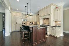 Cream or off-white kitchen with dark brown two-level tiered island.