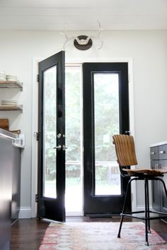 housetweaking.com - black french doors (no mullions- more modern) in white kitchen