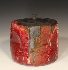 Ceramics by Margaret Curtis at Studiopottery.co.uk - 2013. Ref: 4523 Lidded jar Height 16cm Width 17cmBlack clay with over-pourings of white porcelain slip and Copper red glaze.