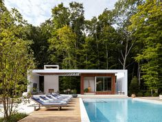 In this landscaped backyard, there's a pool house with an outdoor dining area and a lounge with fireplace. Sun loungers line the length of the swimming pool.