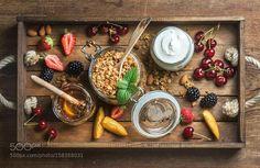 Healthy breakfast ingredients. Oat granola in open glass jar fruit berries and mint on blue...