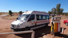 A Britz Sprinter campervan at an antique gas pump in the Australian outback, near Uluru.