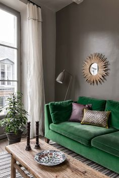 Green velvet sofa and gray walls