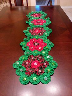 FREE SHIPPING. This table runner is 40 long and 11 wide. It is made from a old quilting design called Grandmas rose garden. It is made up of yoyos arranged in a flower design with green yoyo around each flower like leaves. Each yoyo has a button in the center. The last picture shows the