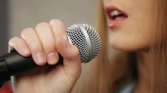 Close-up of singer touching microphone singing - HD stock footage clip