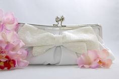 """Plush white matte satin clutch adorned with an elegant bugle beaded bow and jeweled tulip bud clasp. Comes with attachable delicate metal strap.  Size: 10"""" Wide at Bottom & 8"""" Wide at Top, 1 3/4"""" Depth, 4 1/2"""" high"""