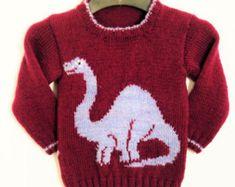 A knitting pattern for a sweater with hood - your youngster will love to wear this dinosaur hoodie! The jumper features a Dinosaur (Velociraptor) on the front and the ribs are knitted in a contrast yarn. This is a striking, warm and trendy sweater for children from 2 to 12 years. Two Colours used. Any Aran/Worsted yarn (10 ply) can be used so long as it matches the tension – 18 sts and 24 rows to 10 cm (4 inches) over stocking stitch using 5mm needles. The garment shown is knitted in H...