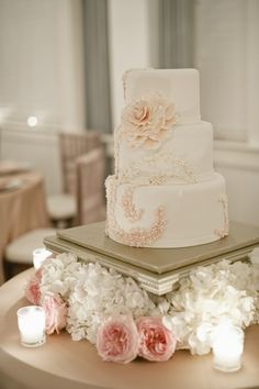 This cake uses tiny sugar flowers in shades of pink to mimic the bride's fabric swirls in her wedding gown.