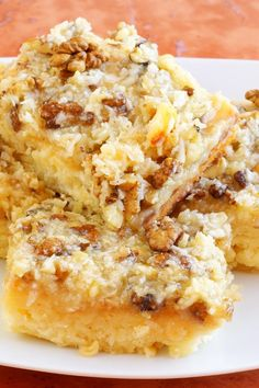Recipe including course(s): Dessert; and ingredients: butter, canola oil, coconut, cream, cream cheese, egg, pecans, powdered sugar, vanilla pudding, water, white cake mix