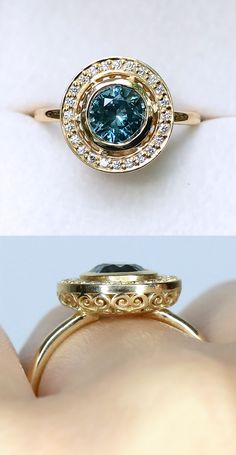 A 1.22 carat glowing Teal Blue GIA Certified Montana Sapphire sits in the center of this lovingly hand crafted antique inspired halo sapphire engagement ring. Inspired by elements of Art Deco, Georgian, and Edwardian design, this ring perfectly brings together antique and contemporary elements for a clean, regal, low-profile, and glamorous look.
