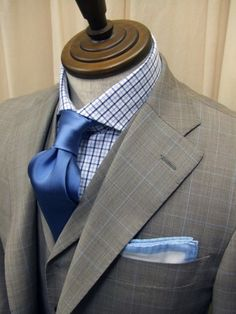 White with blue tattersall pattern dress shirt, blue silk tie, prince of wales check suit and vest. Light blue and white pocket square.