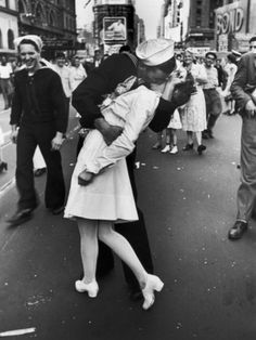 Kiss the War Goodbye. This photo was not taken of a couple greeting lovingly after his return from the war. It was captured by a photographer as the men joyously stormed the streets of NYC. This man grabbed hold of this little lady and planted a wet one right on her lips - I wonder what she was thinking. . .