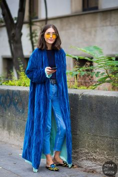Blue long coat with cool 00s yellow glasses.