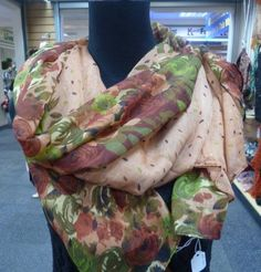 A floral patterned polyester scarf in a mixture of colours, greens, fawns and browns.