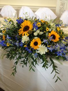 Top table sunflowers, scabious, delphinium, white hebe, thlaspi and eucalyptus parvifolia.