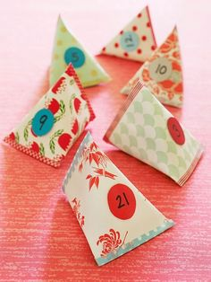 "A bowlful of these DIY treats make a cute and festive way for kids to count down to Christmas. 1. Cut scrapbook paper into 24 4- by 7-inch rectangles. 2. Roll each rectangle into a cylinder as shown and seal the seam with washi tape. 3. Flatten one end of the cylinder and seal it with washi tape. 4. Fill the paper packet with a small toy, candy, or a handwritten ticket for something fun to do (such as ""go out for hot chocolate"" or ""watch Elf in your PJs""). 5. Turn the top of the filled packe..."