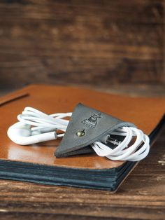 """The Cord Holder is constructed out of a single piece of vegetable tanned leather. It gives you easy way for managing your cords.   Material: - Vegetable tanned leather (1.6 - 2.0 mm thickness) - Metal Stud Closure   Size: - 55 mm (H) x 50 mm (W)  - 2.17 """" (H) x 1.97 """" (W)  Details: - 1..."""
