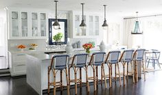 All-white kitchen with a row of industrial-inspired nickel pendant lights over the kitchen island, dark hardwood floors and blue and white striped bar stools at the carrara marble waterfall counter.