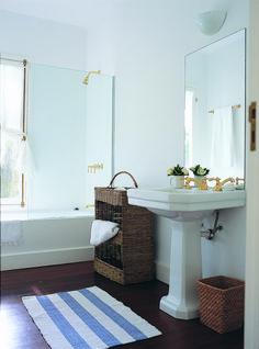 Baño de una casa en Punta del Este, Uruguay, con alfombra en celeste y blanco, piso de madera y mueble en mimbre con cesto haciendo juego.