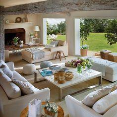 Salón con vigas pintadas de blanco y vistas al jardín