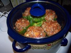Bell peppers are stuffed with ground beef, onion, and rice and topped with spaghetti sauce in a crock pot.