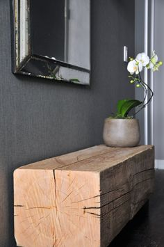 Hallways need love too! Interior design and decor company, Spaces by Jacflash turned a once drab, disorderly hallway into an elegant and luxurious foyer by combining organic elements such as a custom, raw barn beam bench, a charcoal, grasscloth wall covering and a live orchid flower, with industrial and sophisticated features such as a cement planter, a bevelled edge, patina mirror and a wrought iron, glass ball wall sconce.