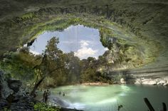 Hamilton Pool is a breathtaking swimming hole outside Austin, Texas. Formed when part of the roof of a circular cavern caved in, the large pool is partially surrounded by a high overhang from which a waterfall drops into the pool.
