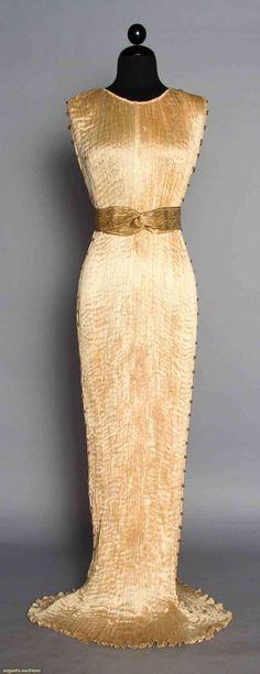 """FORTUNY SILK DELPHOS W/ BOX, 1920-1930s Blond silk pleated sleeveless gown, Murano amber & white glass side seam beads, stencilled cotton sateen 2"""" belt, dress & belt labeled, L 59"""", (hem area dingy & few tiny spots) pleats all tight, excellent; original round cardbox box, black ribbon ties w/ glass beads, round label on lid """"Mariano Fortuny Venise 509 Madison Ave. New York, N.Y."""", 8"""" x 5.5"""", (lid damaged) fair."""
