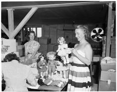 Mrs. Violet Gradwohl, owner of Terri Lee doll factory at Apple Valley, inspects some dolls.  Victorville layout, 1952 :: Los Angeles Examiner Collection, 1920-1961