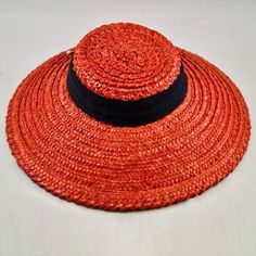Cherry-red straw hat with blue ribbon (front view) | Small, flat crown and a great wide brim which gives the hat a touch of class with the added benefit of sun-blocking protection | The big, bold bow at the bottom is permanently knotted but features two small bands of elastic so it can be slipped comfortably under the chin
