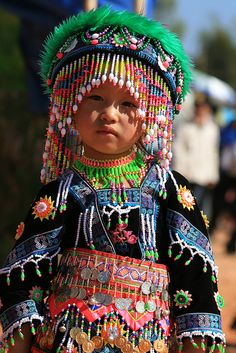 A child from the Hmong ethnic group in Laos dresses in colourful costume for Chinese New Year.