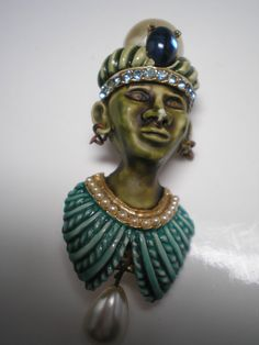 HAR Brooch is either a Princess or Genie and the face is an olive  green. Turbin has a faux Pearl and faux Sapphire and clear rhinestones  set at the