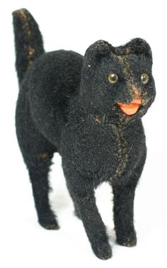 "Very early German cat candy container with fur and arching back, 6"" long by 5½"" tall. Head comes out to reveal candy space. Cat has glass eyes, composition mouth and fur is in good condition."