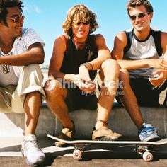 Stock Photo : portrait of three young men sitting on a wall with a skateboard