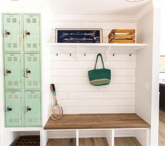 Vintage mudroom features built-in metal mint green locker cabinets next to a built-in wood top bench under hooks and a single shelf.