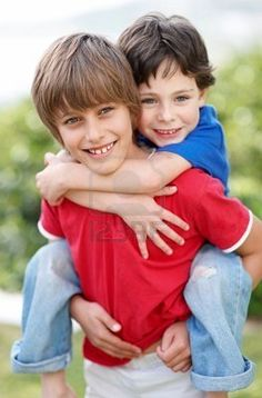 Portrait of happy big brother giving his little brother a piggyback ride - Outdoors Stock Photo