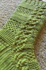These socks combine garter and lace bands off-set with a cable that runs down the outside of the sock. Top-down socks that match my Green Beryl Shawl. An easy-to-remember pattern, and the third in my VBM Sock Collection 1. These are available for individual purchase or as part of the collection. As with all of the other patterns in the collection, the pattern includes both written and charted instructions.