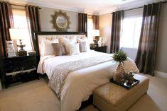 master bedroom. gold starburst mirror. creme bedding. bronze accents. trufted headboard. espresso furniture. chocolate drapes. foo dog sculpture. gold accents.