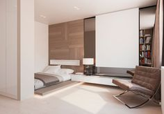 A Le Corbusier style chair is a comfortable landing place in the cozy, wood paneled bedroom.