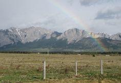 A rainbow guarding Yamnuska across Morley Flats near Kananaskis Country west of Calgary, Alberta, Canada